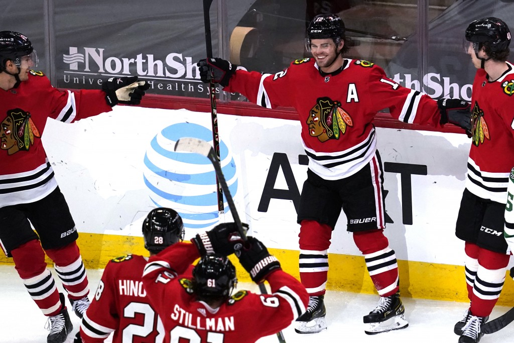 Chicago Blackhawks left wing Alex DeBrincat, second from right, smiles after scoring his second goal against the Dallas Stars, during the third period...
