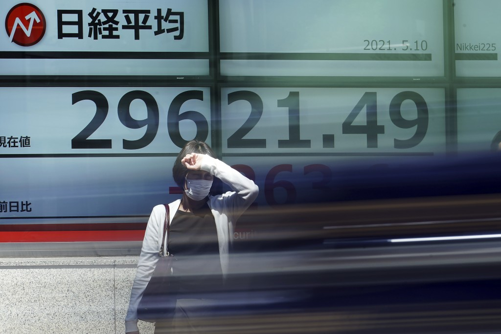 As a vehicle drives by, a woman wearing a protective mask stands in front of an electronic stock board showing Japan's Nikkei 225 index at a securitie...