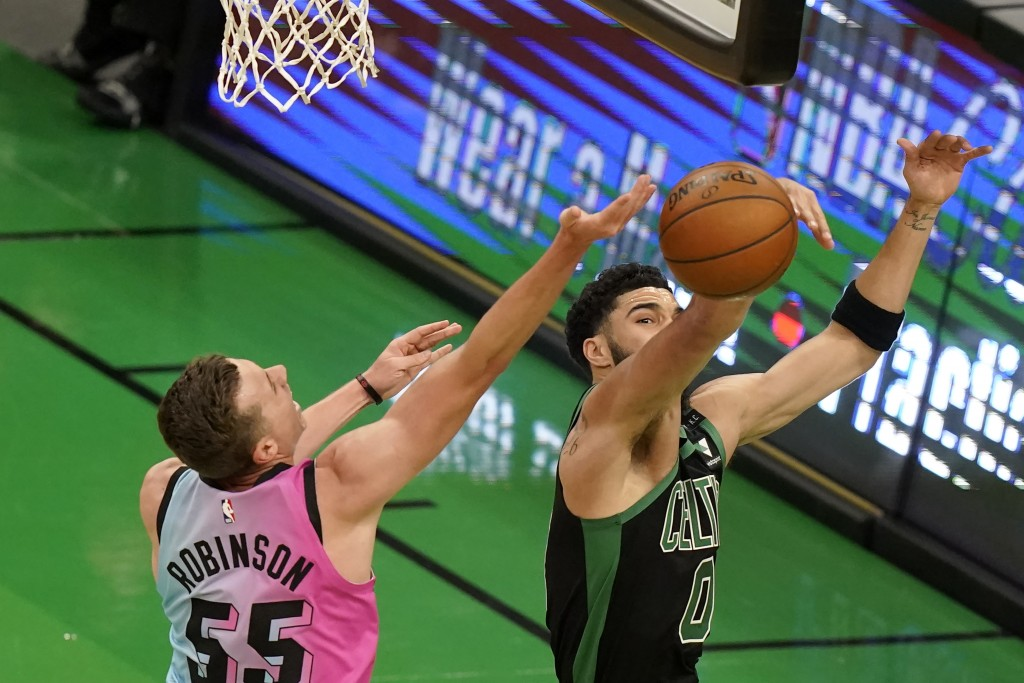 Miami Heat's Duncan Robinson, left, drives toward the basket as Boston Celtics' Jayson Tatum, right, deflects the ball in the first half of a basketba...