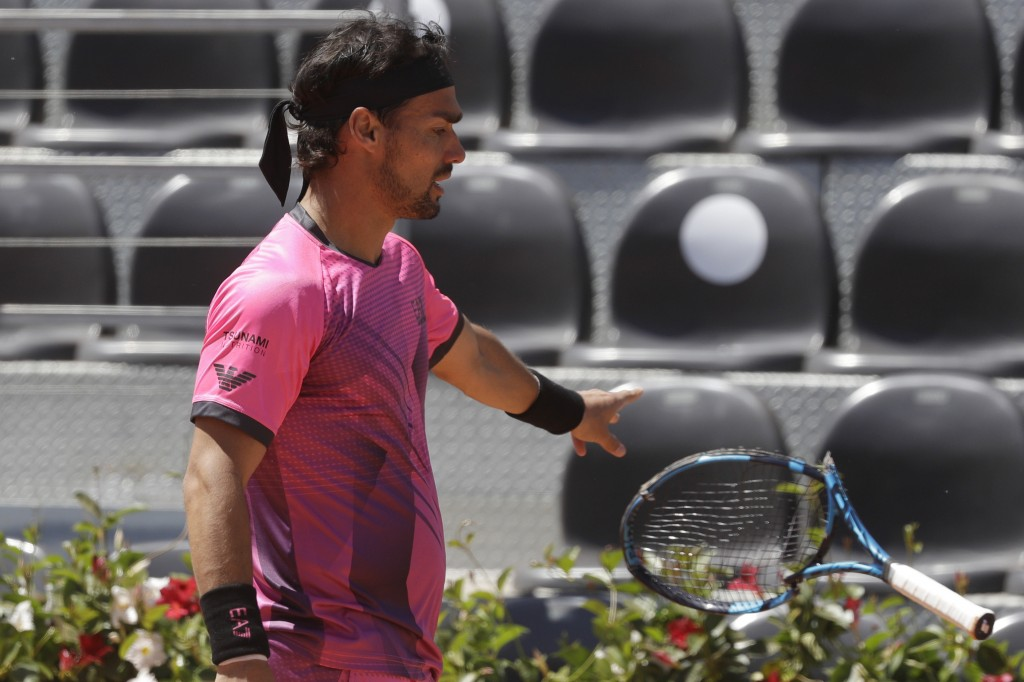 Italy's Fabio Fognini throws away his racket after breaking it during his match against Japan's Kei Nishikori at the Italian Open tennis tournament, i...