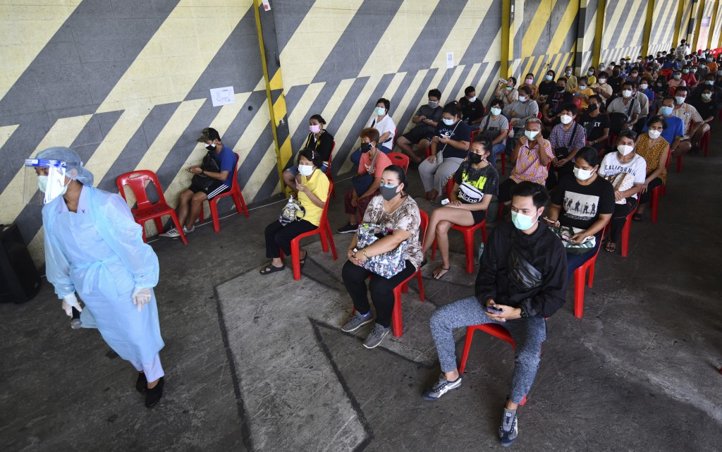 Residents of the Klong Toey area, a neighborhood with a recent rise in coronavirus cases, waiting to receive Sinovac COVID-19 and the AstraZeneca COVI...