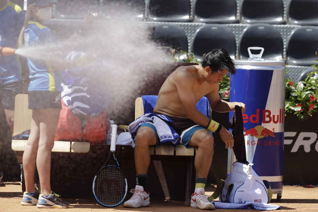 Japan's Kei Nishikori changes his shirt during a match against Italy's Fabio Fognini at the Italian Open tennis tournament, in Rome, Monday, May 10, 2...