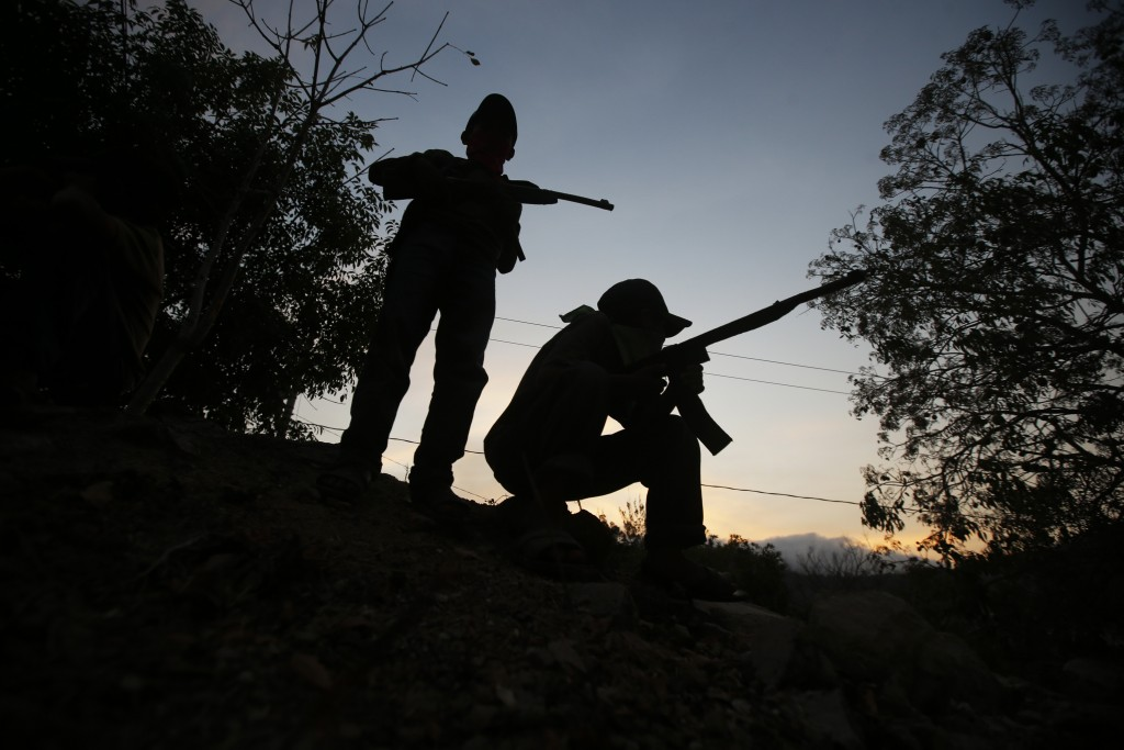 With fake rifles, children guard the entrance of their town, Ayahualtempa, in Guerrero state, Mexico at dusk Wednesday, April 28, 2021. Nahua Indigeno...