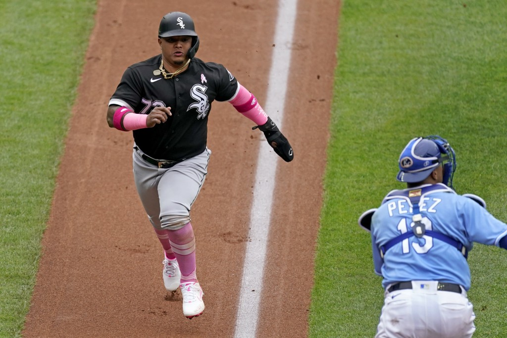 Chicago White Sox's Yermin Mercedes runs home past Kansas City Royals catcher Salvador Perez to score on a sacrifice fly hit by Leury Garcia during th...