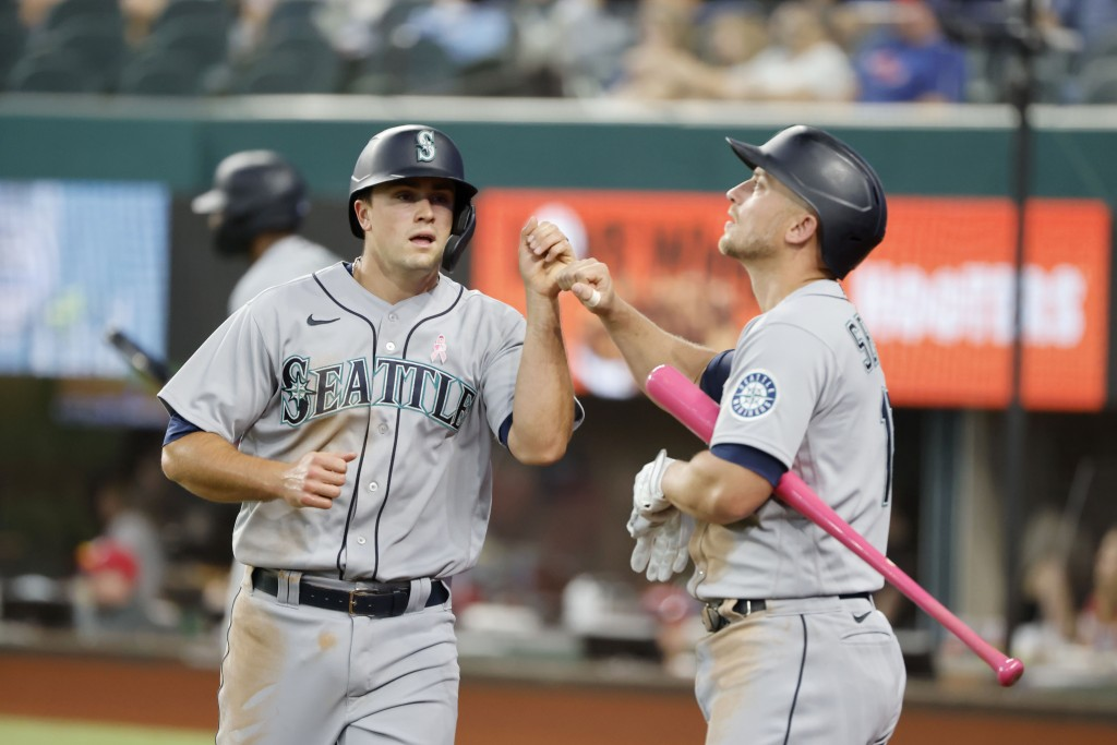 Seattle Mariners Evan White, left, is congratulated by Kyle Seager, right, after scoring a run against the Texas Rangers during the fifth inning of a ...