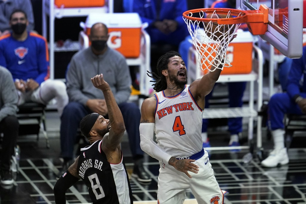 New York Knicks guard Derrick Rose (4) scores past Los Angeles Clippers forward Marcus Morris Sr. (8) during the first half of an NBA basketball game ...