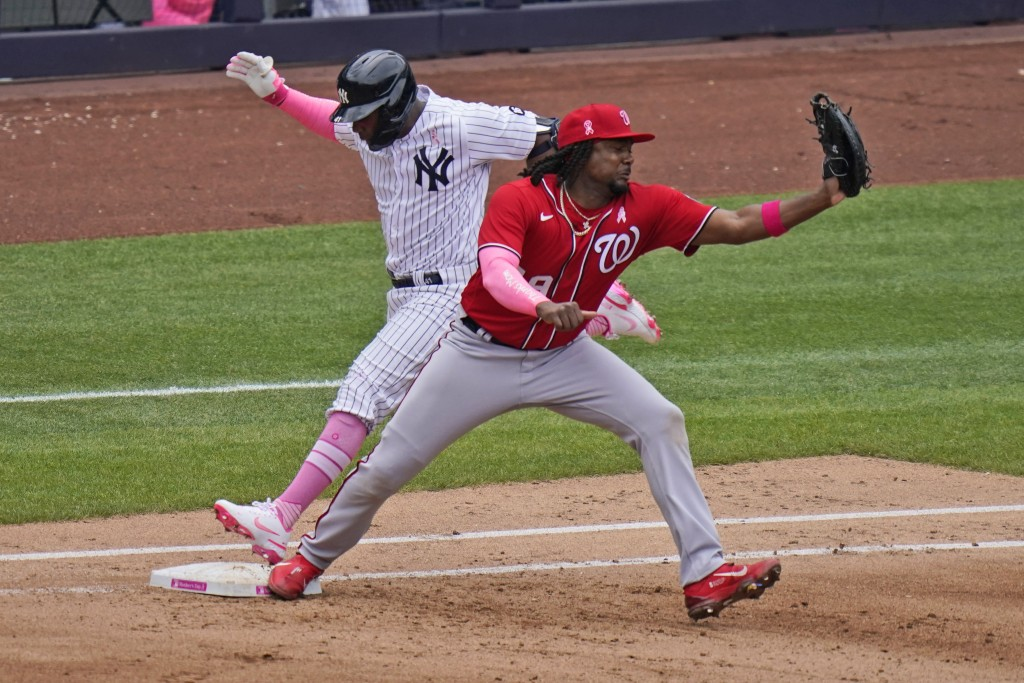 New York Yankees' Miguel Andujar, left, cannot beat the throw to Washington Nationals first baseman Josh Bell during the fourth inning of a baseball g...