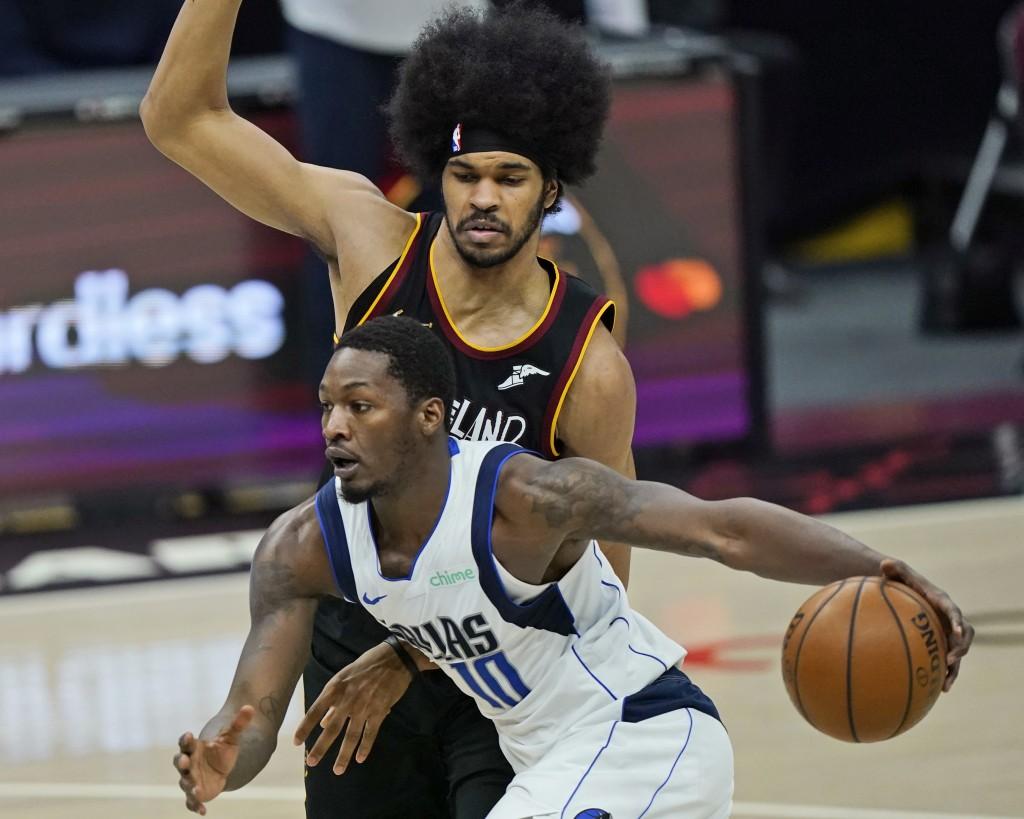 Dallas Mavericks' Dorian Finney-Smith, front, drives against Cleveland Cavaliers' Jarrett Allen during the second half of an NBA basketball game Sunda...