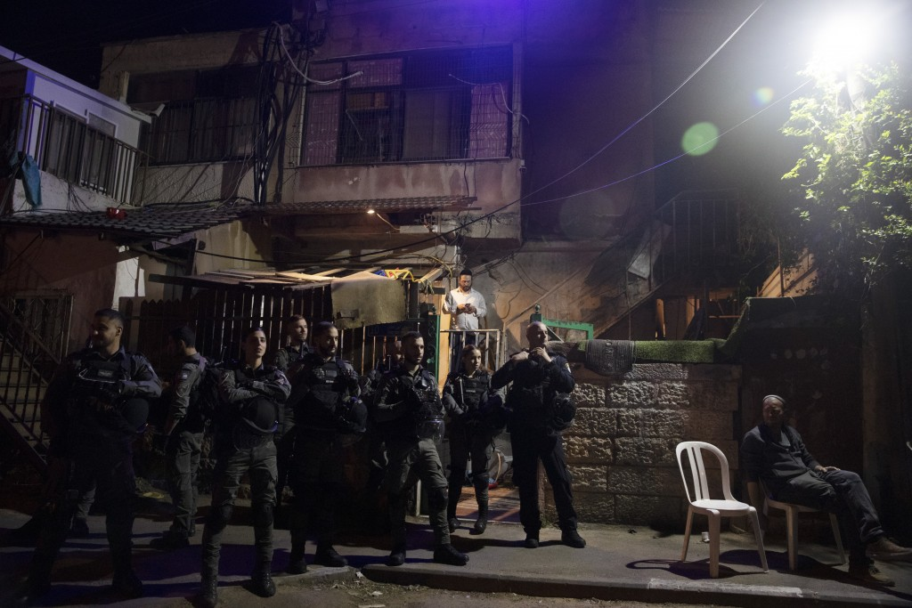 FILE - In this May 5, 2021 file photo, Israeli police stand guard in front of a Palestinian home occupied by settlers during a protest on the eve of a...
