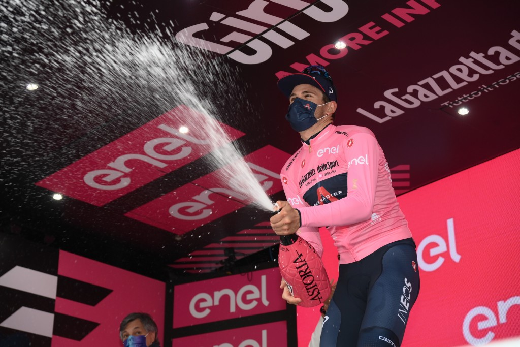 Italy's Filippo Ganna wears the pink jersey of the race's overall leader as he celebrates on the podium after completing the third stage of the Giro d...