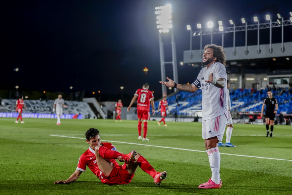 Real Madrid's Marcelo, right, reacts during the Spanish La Liga soccer match between Real Madrid and Sevilla at the Alfredo di Stefano stadium in Madr...