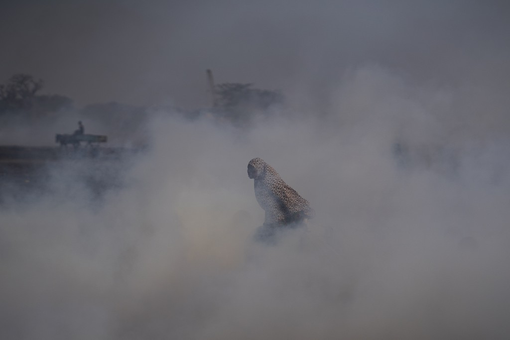 A woman working on a fish processing site walks through the thick smoke coming from burning peanut shells used to cure fish on Bargny beach, some 35 k...