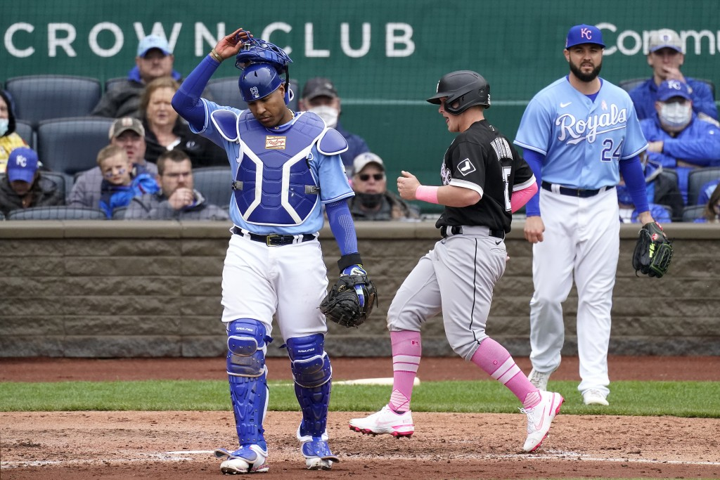 Chicago White Sox's Andrew Vaughn runs between Kansas City Royals catcher Salvador Perez and pitcher Jakob Junis (24) to score on a single by Leury Ga...