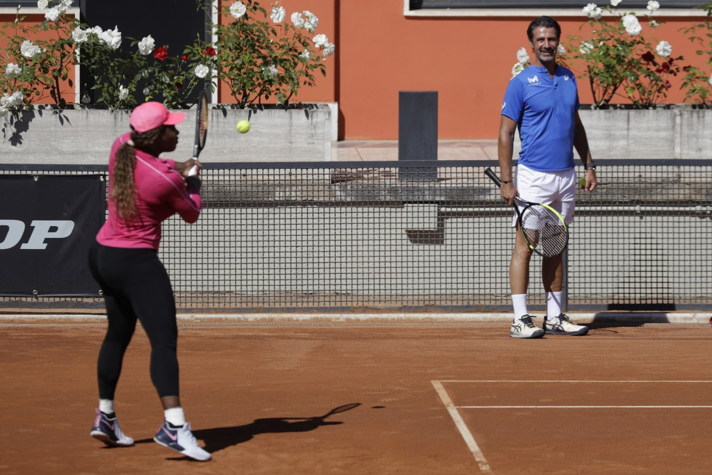 Serena Williams returns the ball as her coach Patrick Mouratoglou, right, watches her during a training session at the Italian Open tennis tournament,...
