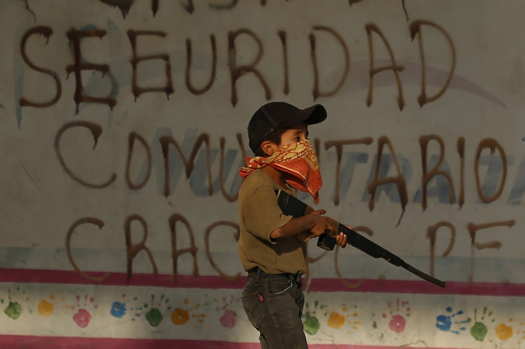 A child practices with a fake, wooden rifle during a display for the media in an attempt to attract the federal government's attention to the dangers ...