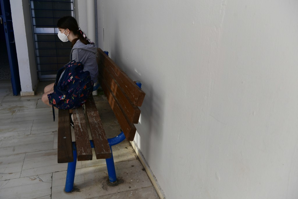 A student wearing a face mask to help curb the spread of the coronavirus, sits on a bench at a junior high school in Athens, Monday, May 10, 2021. Mor...