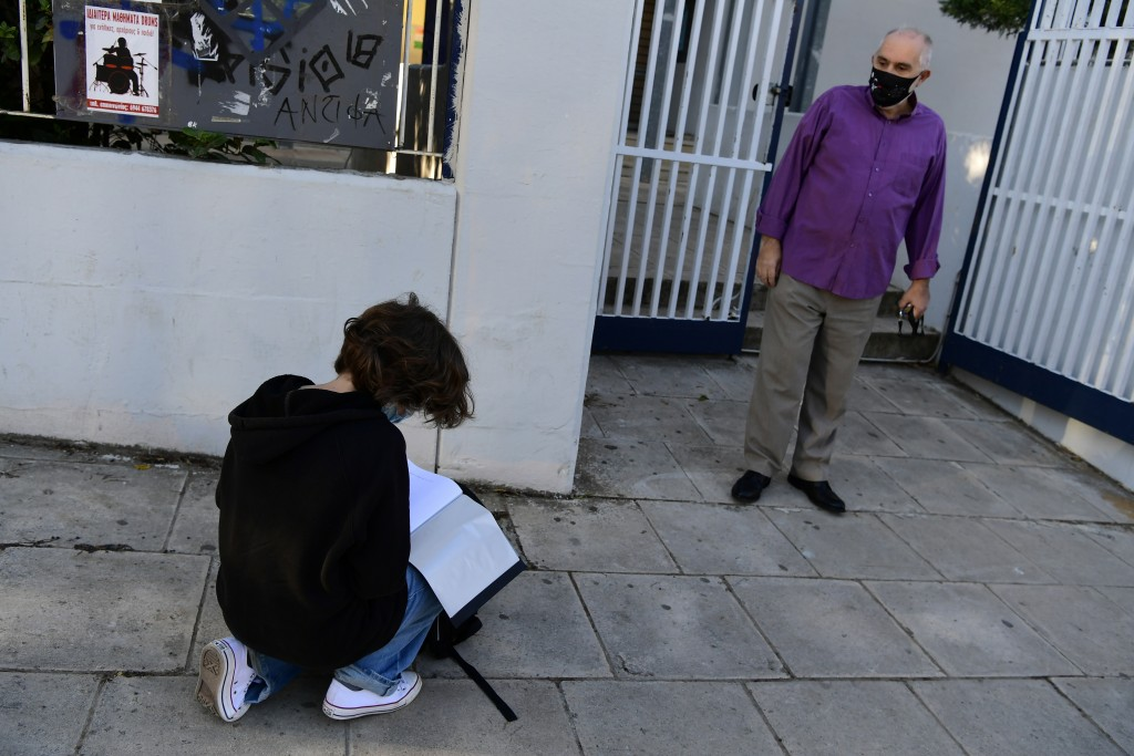 A student looks for his document stating a negative COVID-19 self-test as a teacher waits at the entrance of the school in Athens, Monday, May 10, 202...