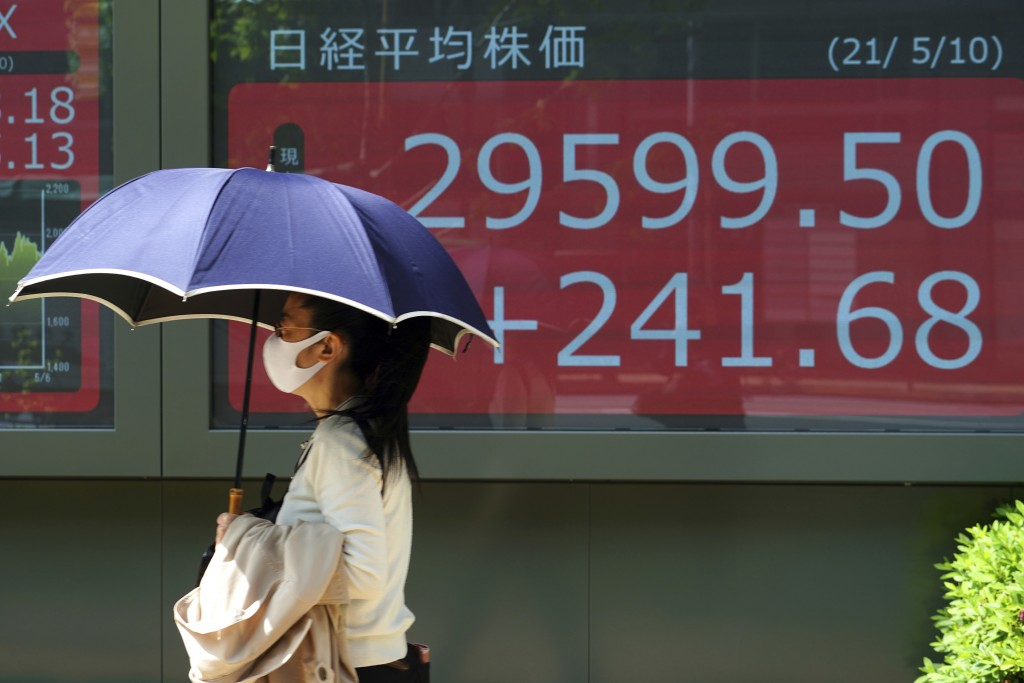A woman wearing a protective mask walks in front of an electronic stock board showing Japan's Nikkei 225 index at a securities firm Monday, May 10, 20...