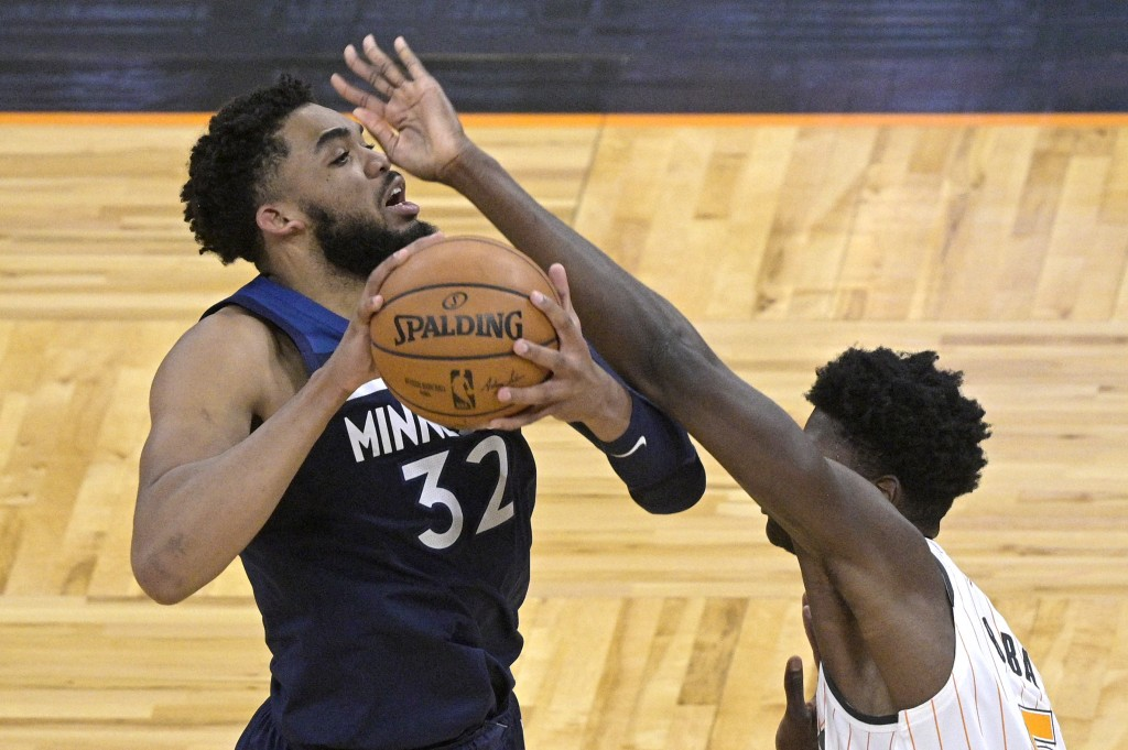 Minnesota Timberwolves center Karl-Anthony Towns (32) is fouled by Orlando Magic center Mo Bamba (5) during the first half of an NBA basketball game S...
