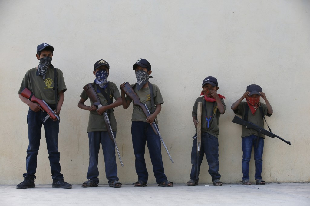 Children hold their training weapons, some real and some fake, during a display for the media designed to attract the federal government's attention t...