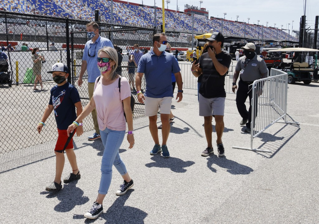 Fans walk through the garage area before a NASCAR Cup Series auto race at Darlington Raceway, Sunday, May 9, 2021, in Darlington, S.C. It is the first...