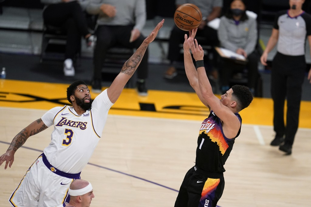 Phoenix Suns guard Devin Booker, right, shoots over Los Angeles Lakers forward Anthony Davis (3) during the first half of an NBA basketball game Sunda...
