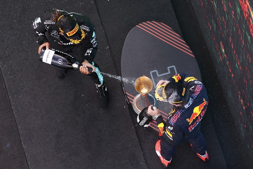 Winner Mercedes driver Lewis Hamilton of Britain sprays second placed Red Bull driver Max Verstappen of the Netherlands, right, on the podium of the S...