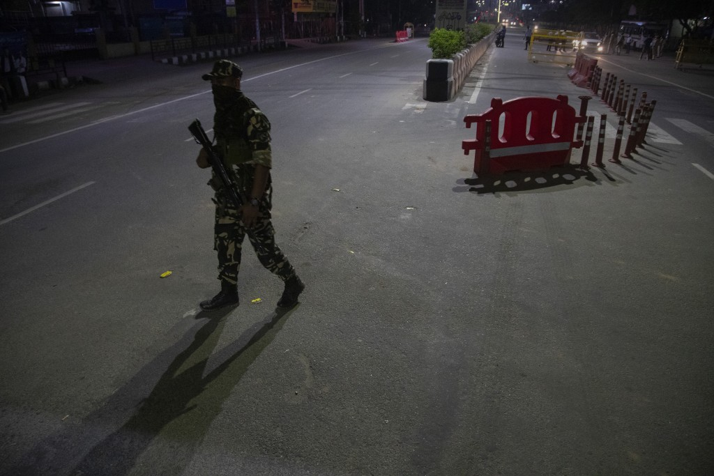 An Indian paramilitary person guards during a night curfew to curb the spread of coronavirus in Gauhati, Assam, India, Sunday, May 9, 2021. (AP Photo/...