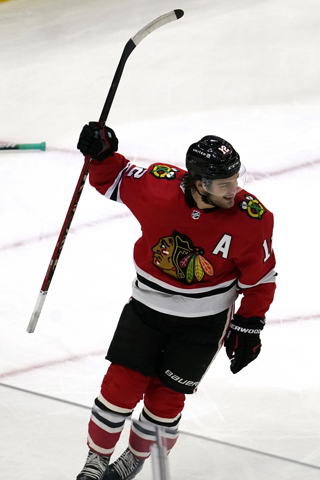 Chicago Blackhawks left wing Alex DeBrincat celebrates after scoring a goal during the first period of an NHL hockey game against the Dallas Stars in ...