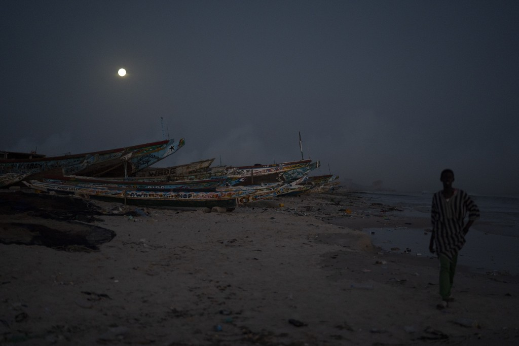A man walks past pirogues used as fishing boats as the full moon rises over Bargny, Senegal, some 35 kilometers (22 miles) east of Dakar, Senegal, Mon...