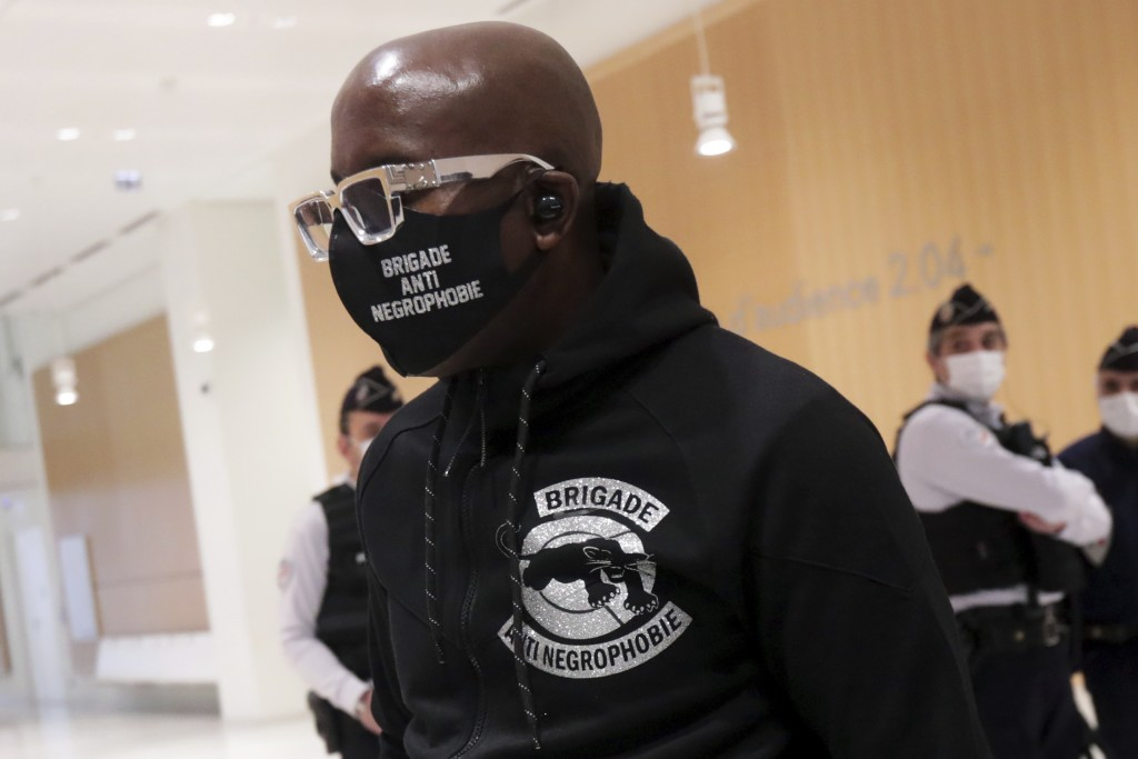An activist from a group called the Anti-Negrophobia Brigade, Franco Lollia, wears a face mask reading «Anti-Negrophobia Brigade» as he arrives at t...