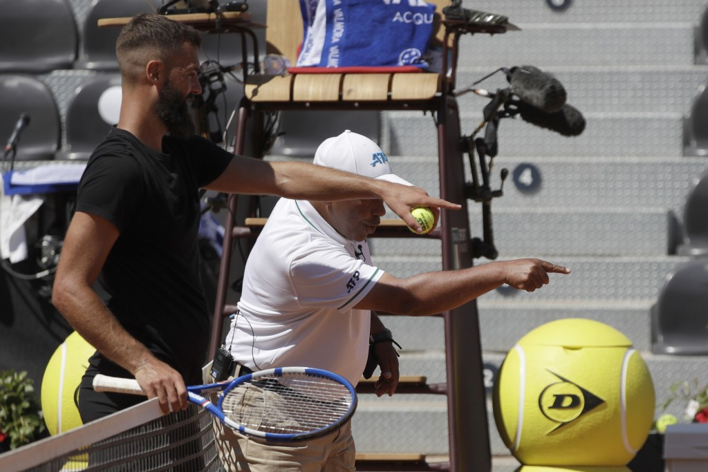 France's Benoit Paire, left, points to a mark left by a ball he shot on the line as he argues with the umpire during his match with Italy's Stefano Tr...