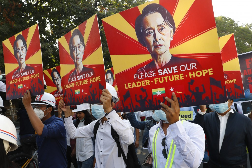 FILE - In this Feb. 15, 2021, file photo, engineers hold posters with an image of deposed Myanmar leader Aung San Suu Kyi as they hold an anti-coup pr...