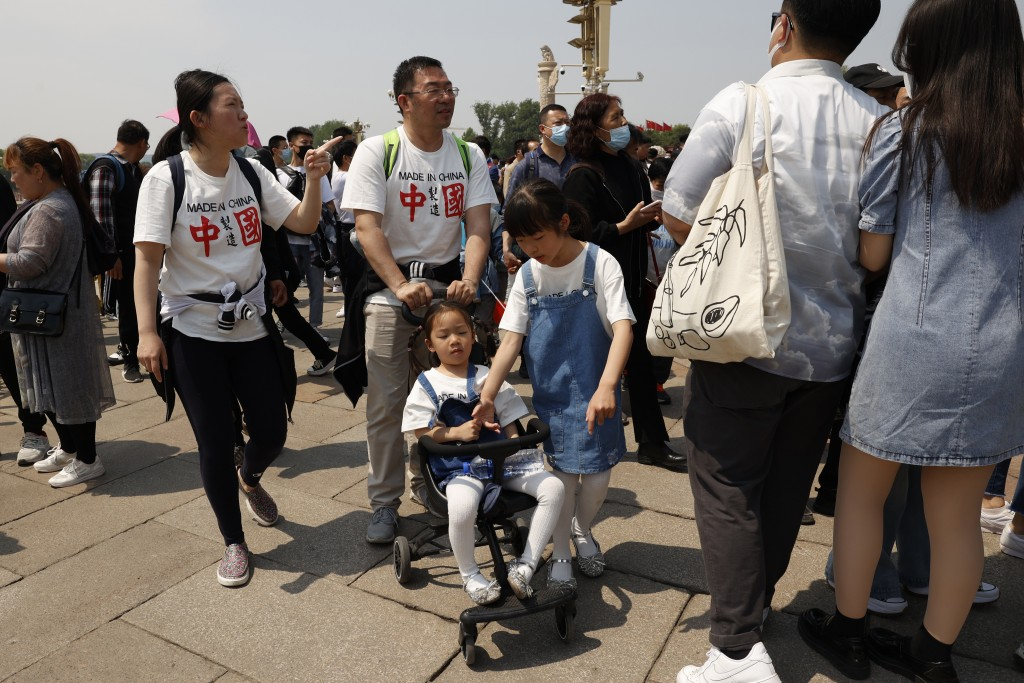 """Residents wearing t-shirts which reads """"Made In China"""" visit Tiananmen Gate with two children in Beijing on May 3, 2021. China's population growth is ..."""