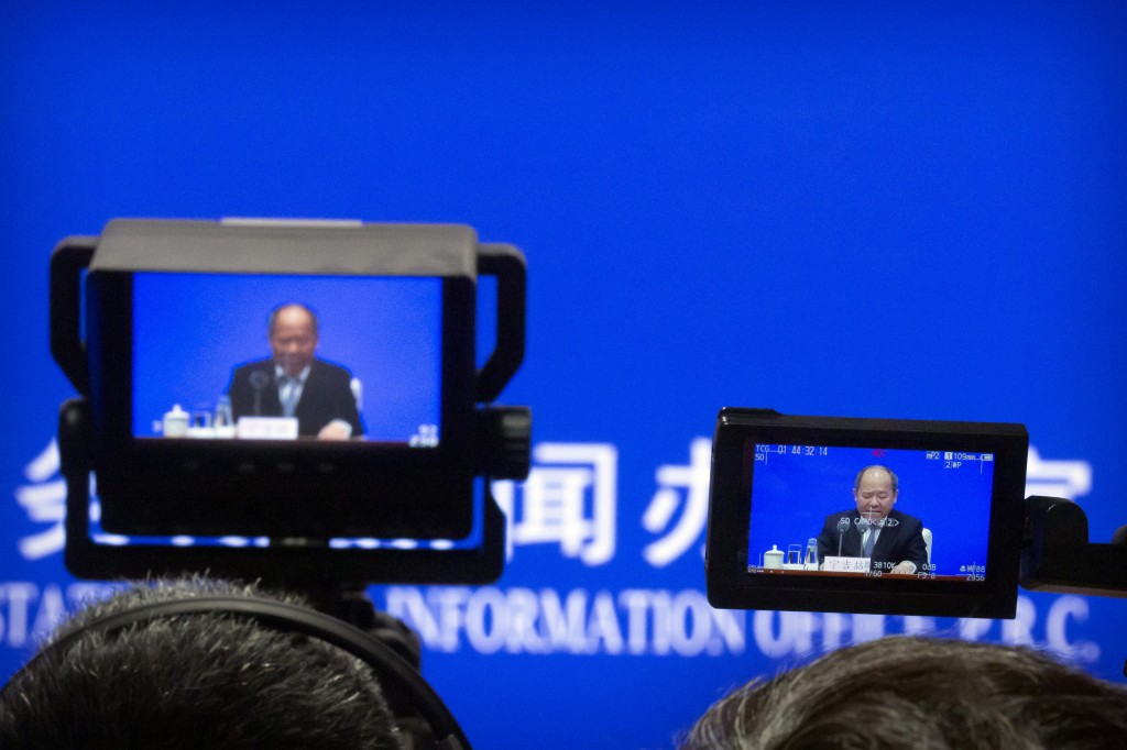 Video screens show Ning Jizhe, commissioner of China's National Bureau of Statistics, as he speaks during a press conference at the State Council Info...