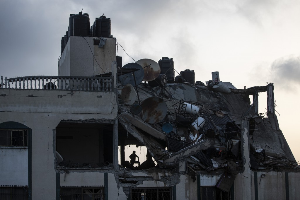 A Palestinian searches for survivors under the rubble of a destroyed rooftop of a residential building which was hit by Israeli missile strikes, at th...