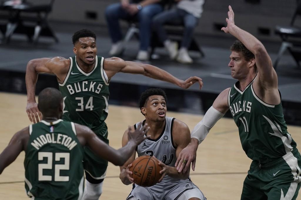 San Antonio Spurs forward Keldon Johnson (3) looks to score against Milwaukee Bucks defenders Khris Middleton (22), Giannis Antetokounmpo (34) and Bro...