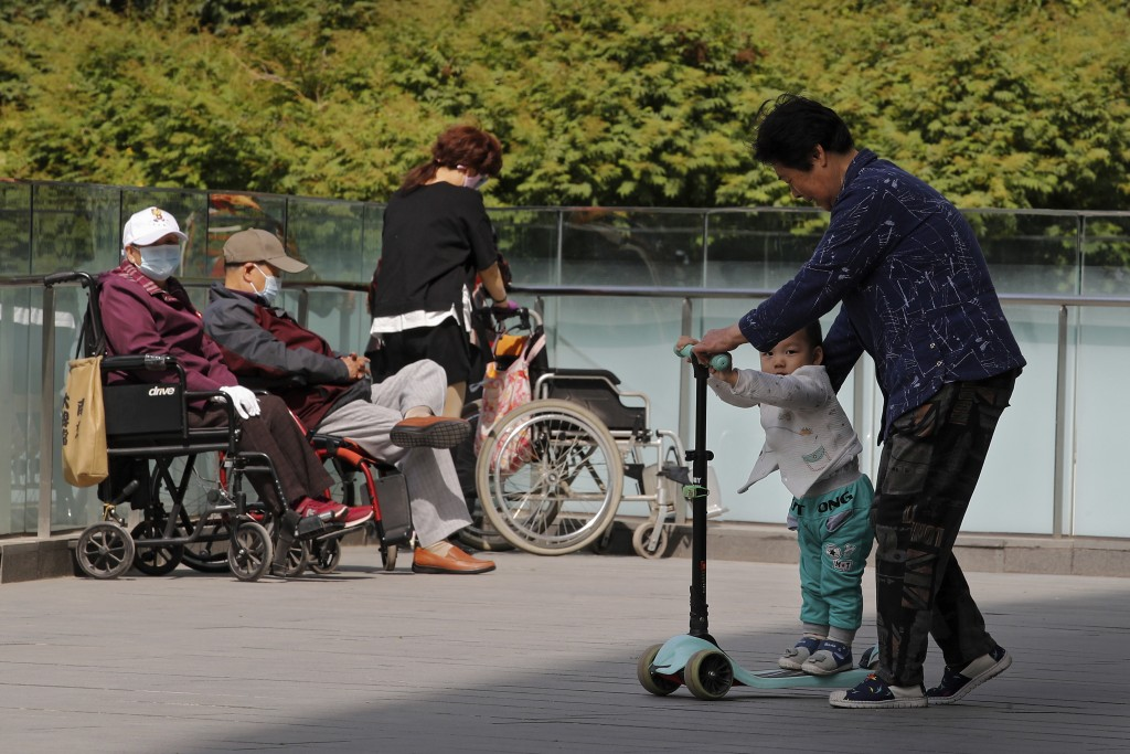 A woman plays with a child near elderly people on wheelchairs sunbathing on a compound of a commercial office building in Beijing on Monday, May 10, 2...