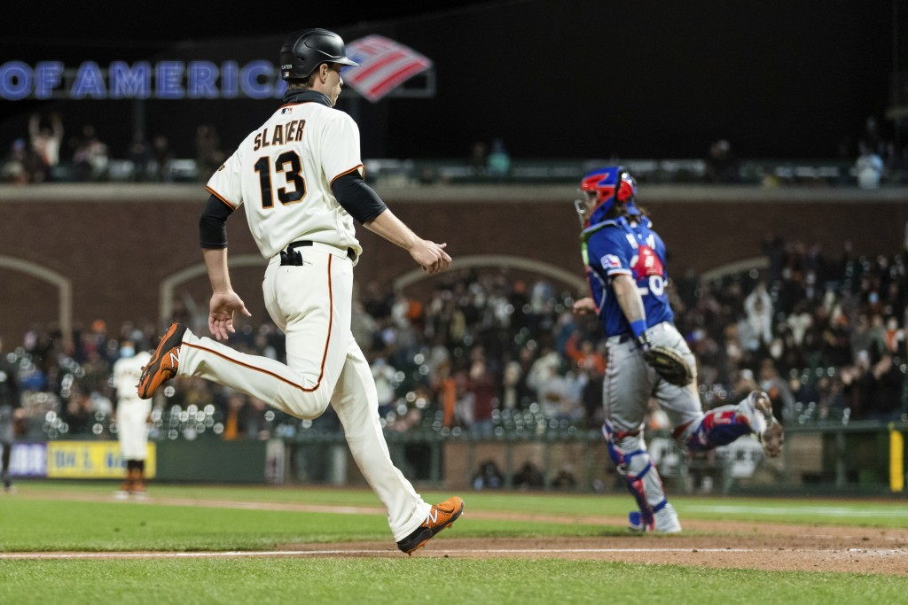 San Francisco Giants' Austin Slater (13) scores a run against the Texas Rangers during the seventh inning of a baseball game in San Francisco, Monday,...