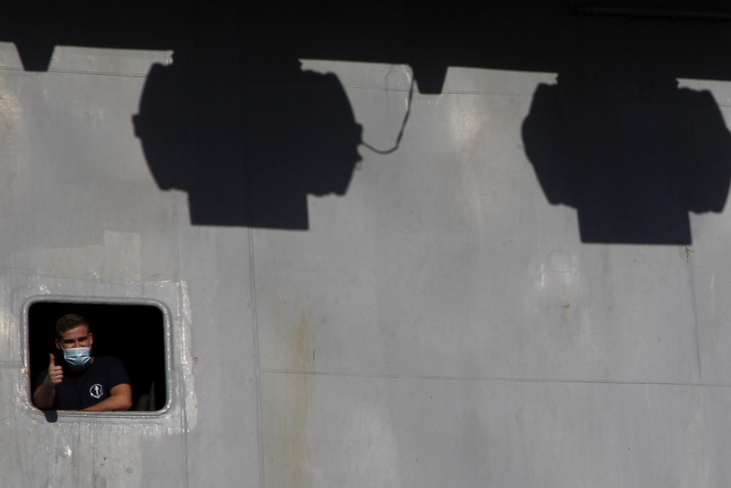 A French crew member is seen of a window on France's nuclear-powered aircraft carrier Charles de Gaulle at Limassol port, Cyprus, Monday, May 10, 2021...