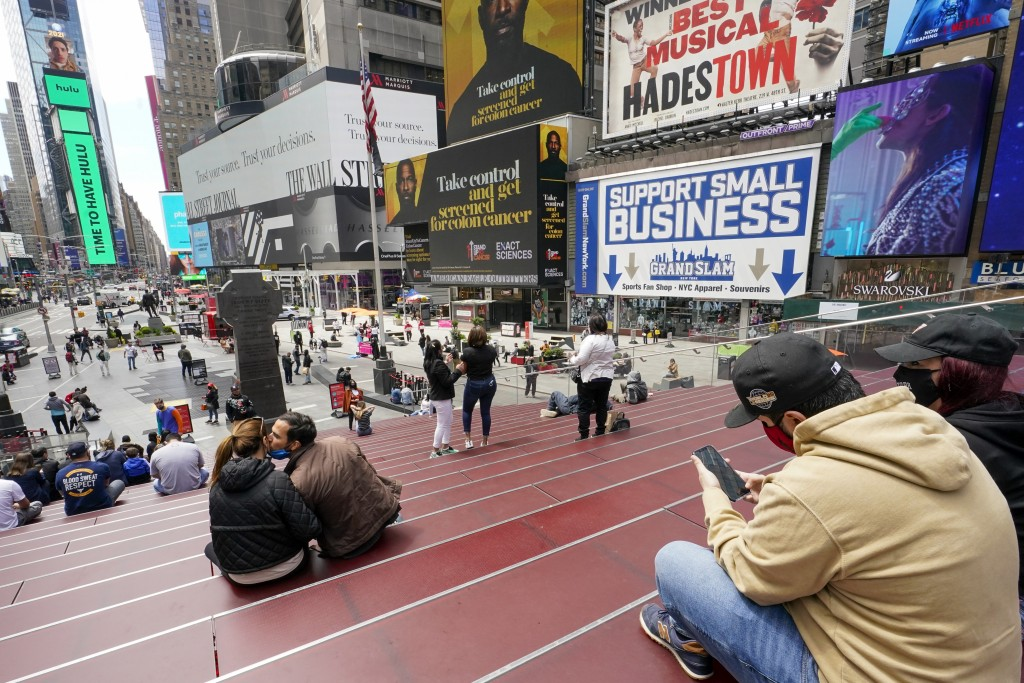 Visitors to New York's Time Square take in the view from the TKTS stairway, Tuesday, April 27, 2021, in New York. In recent weeks, tourism indicators ...