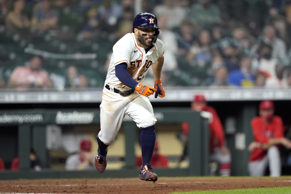 Houston Astros' Jose Altuve runs down the first base line after a bunt single against the Los Angeles Angels during the fourth inning of a baseball ga...