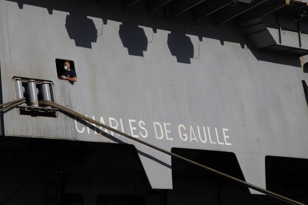 A French crew member is seen of a window at France's nuclear-powered aircraft carrier Charles de Gaulle at Limassol port, Cyprus, Monday, May 10, 2021...