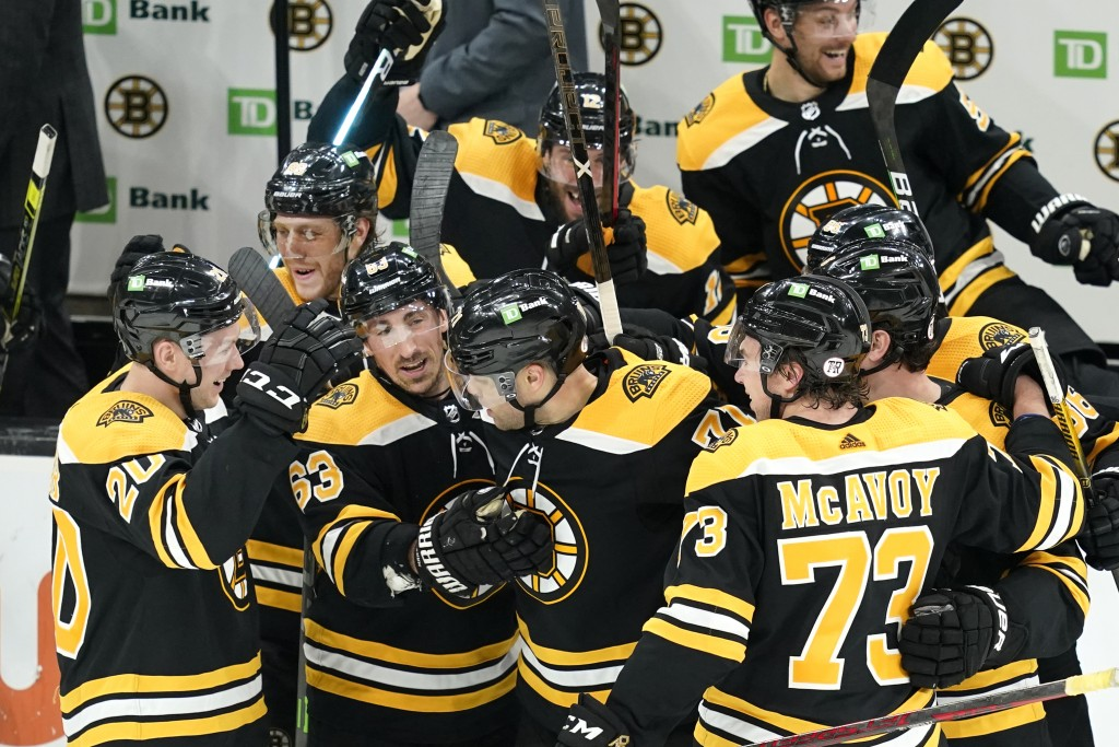 Boston Bruins' Brad Marchand (63) and others surround left wing Taylor Hall, center, to celebrate his winning goal in the overtime period of an NHL ho...