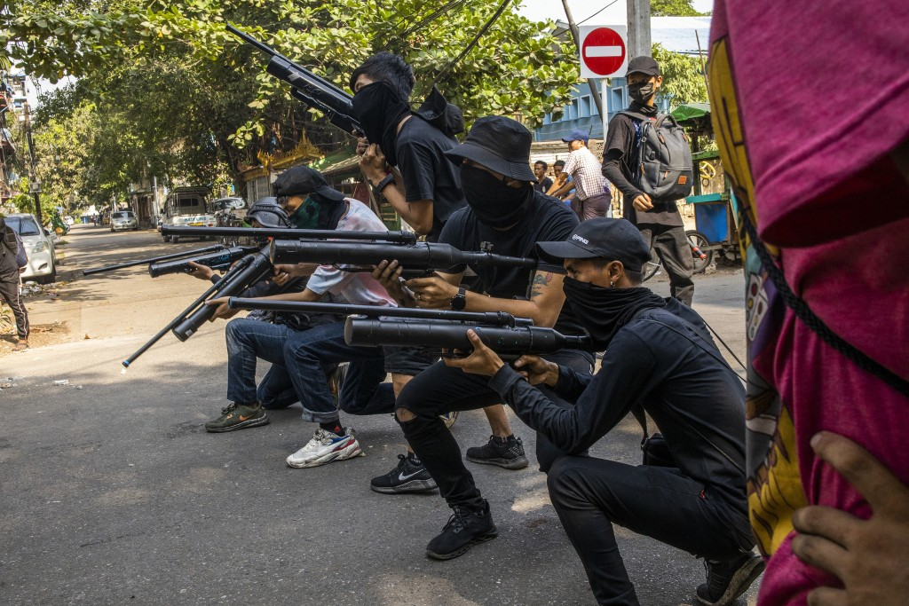 FILE - In this April 3, 2021, file photo, anti-coup protesters line in formation with homemade air rifles during a demonstration against the military ...