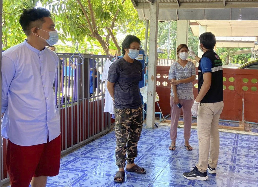In this photo released by the San Sai District Administrative Office, a Thai officer checks the temperature of journalists working for Democratic Voic...