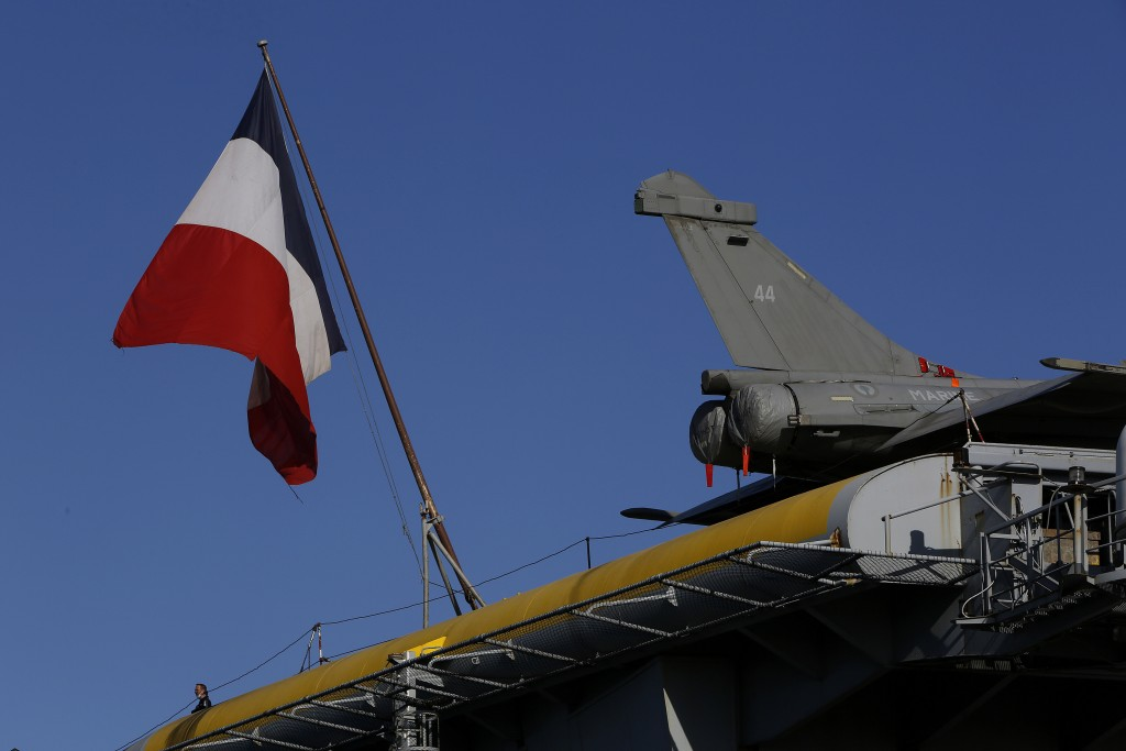 A French crew member stands next of a French flag and an aircraft on the France's nuclear-powered aircraft carrier Charles de Gaulle at Limassol port,...