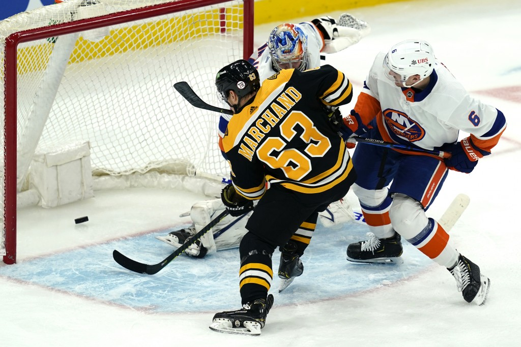 Boston Bruins center Brad Marchand (63) scores past New York Islanders goaltender Semyon Varlamov as Islanders defenseman Ryan Pulock (6) tries to def...