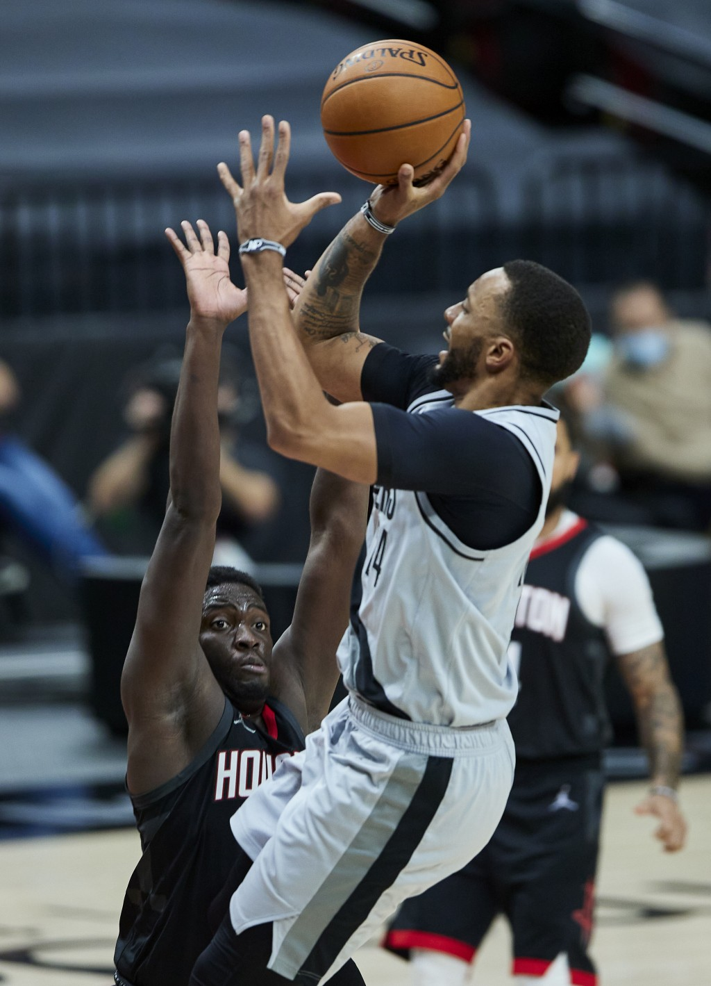 Portland Trail Blazers forward Norman Powell, right, shoots over Houston Rockets forward Khyri Thomas during the second half of an NBA basketball game...