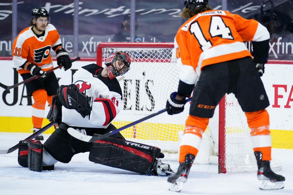 Philadelphia Flyers' Sean Couturier (14) scores a goal past New Jersey Devils' Scott Wedgewood (41) during the second period of an NHL hockey game, Mo...